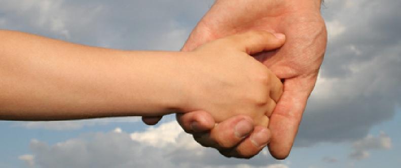 Eine erwachsene Hand hält eine Kinderhand