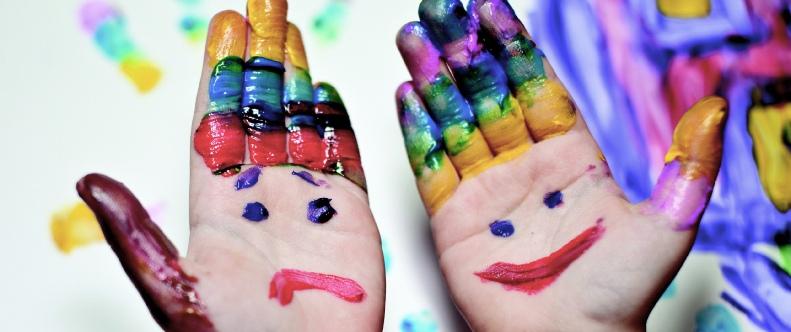 Mit lachendem und weinenden Gesicht bemalte Kinderhände