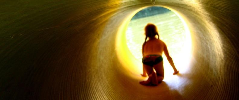 Ein Kind krabbelt durch eine dunkle Röhre zum Licht am Ausgang
