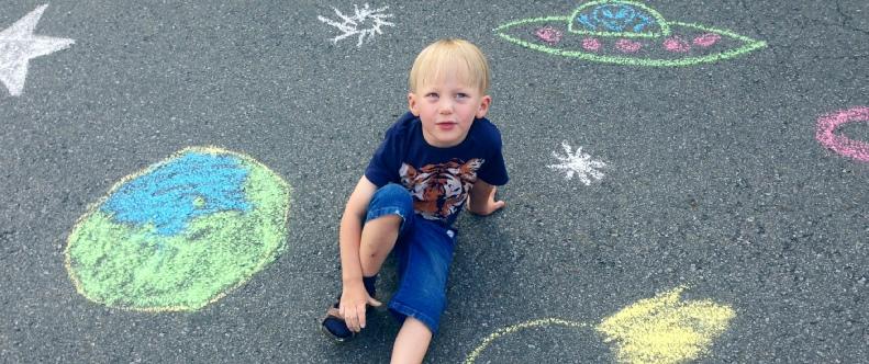 Ein kleiner Junge hat ein Ufo und Sterne auf die Straße gemalt
