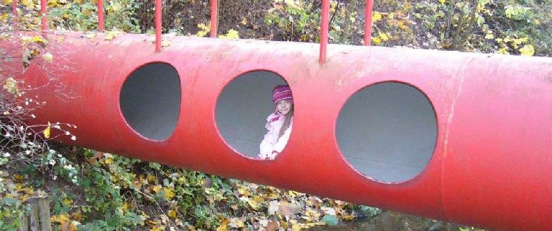 Amelie krabbelt durch eine rote Röhre, die über einem Bachbett liegt
